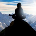 Frau sitzt im Yogasitz auf Bergspitze