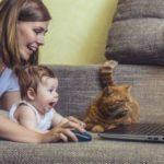 Frau mit Kind und Katze am Laptop